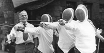 An old black and white photograph shows an instructor teaching three visually impaired fencers in full gear how to fence.