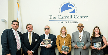 Carroll Center for the Blind President Gregory Donnelly stands beside Former MCB Commissioner Paul Saner and four Carroll Society Award winners holding their awards.