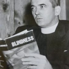 A black and white photo of Father Carroll holding up a copy of his newly published book.