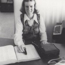 A black and white photo of a young woman using the prototype Optacon machine. She runs a small black probe connected to a larger device over a page in a book.