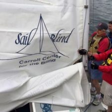 A group of three blind and visually impaired sailors rig a sail on a sailboat that features the SailBlind logo.