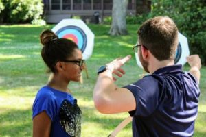 an archery instructor demonstrates proper firing technique to a low vision teen.]