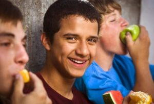 three teenagers laugh together as they eat their lunches.]