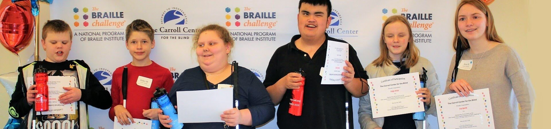 A group of 6 young visually impaired teens stand together holding completion certificates at the New England Regional Braille Challenge.