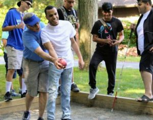a group of teenagers with varying degrees of visual impairment play bocce using an audible adaptive device.