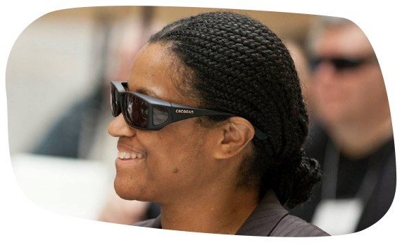 A blind woman wearing sunglasses laughs with others at an advocacy event at the Massachusetts State House.