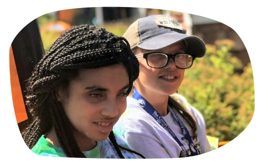 Two teenage girls with visual impairments smile together on a ride at an amusement park.