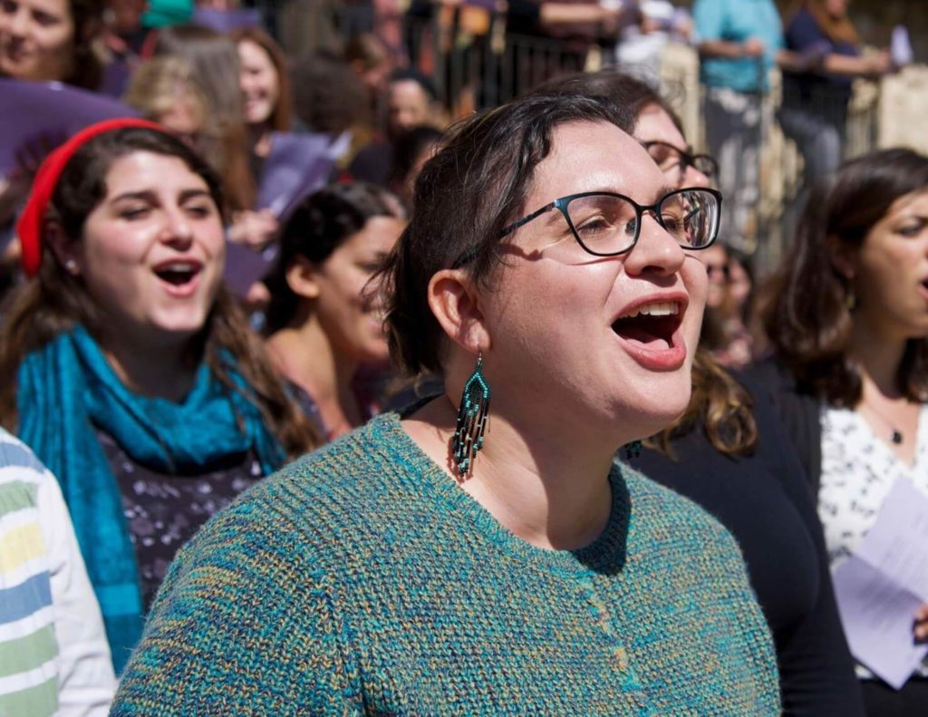 A woman sings loudly beside many other audience members at a Koolulam performance.