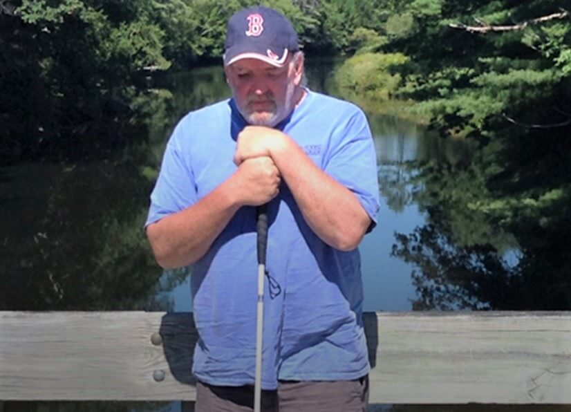 Deon Lyons stands on a bridge over a small river holding his cane. Hand over hand on top of his cane, he rests his chin on top of it while deep in thought.