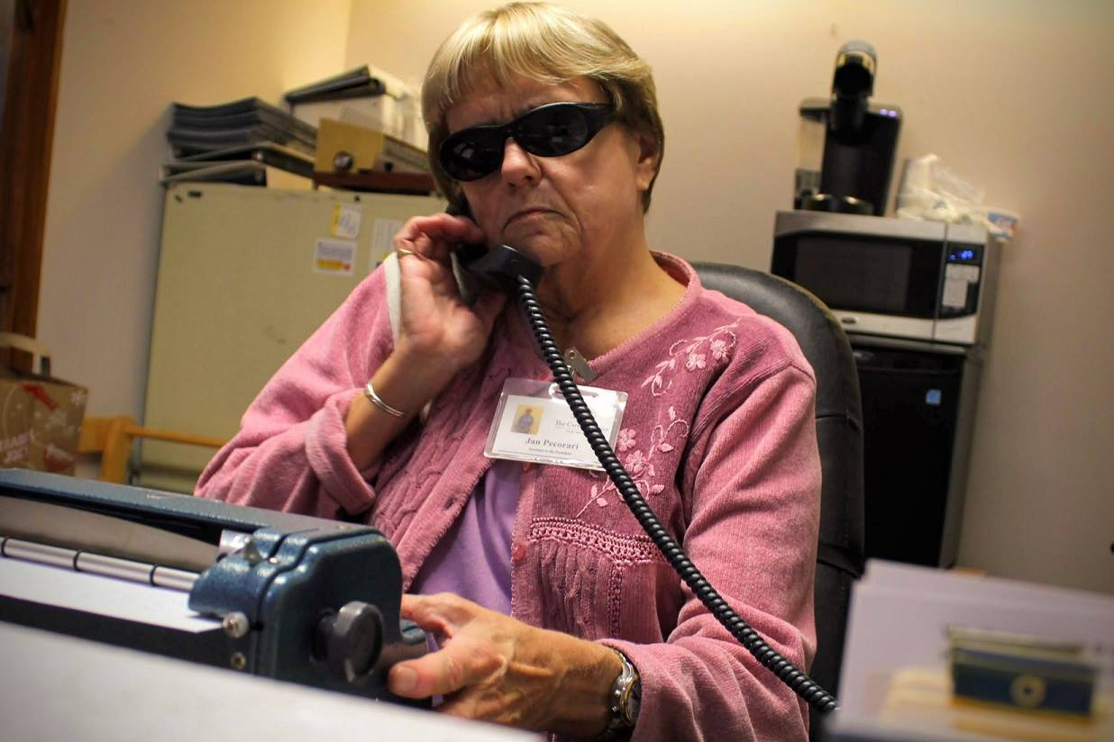Jan Pecorari, Executive Assistant to the President, talks on a corded phone while typing on the Perkins Brailler on her desk.