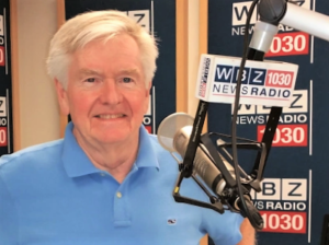 Wearing a blue polo shirt, Dan Rea smiles behind a large microphone with the WBZ 1030 NewsRadio logo on it.