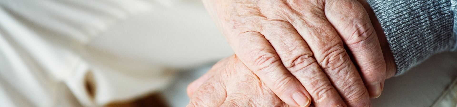 The hands of an elderly person interlock atop their lap.