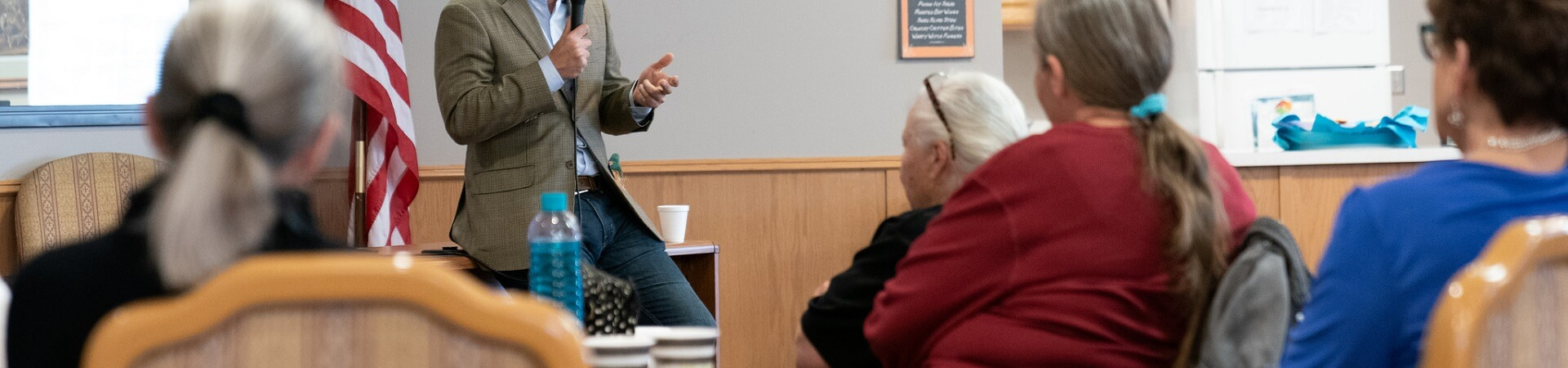 A man holding a microphone presents to a crowd of elderly people at a senior center.