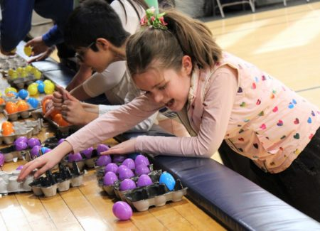 Freshman category winner Hannah works with her fellow participants to solves a braille puzzle made out of egg cartons.