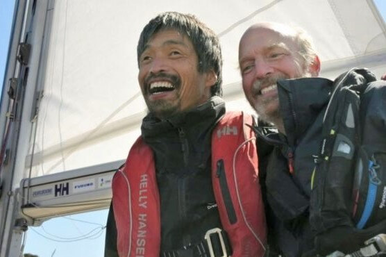 Blind sailor, Mitsuhiro Iwamoto (left), celebrates his 2-month journey of crossing the Pacific ocean with his navigator, Doug Smith (right) on the bow of their sail boat.