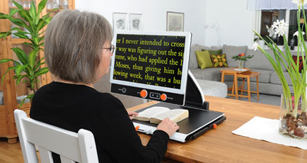 A woman sits down at her desk to read a book using a portable desktop video magnifier.