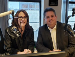 Two people sit in a recording studio. Vicki Green, host of Community Conversations on WXLO 104.5FM is on the left. Carroll Center for the Blind President and CEO, Greg Donnelly, is on the right.