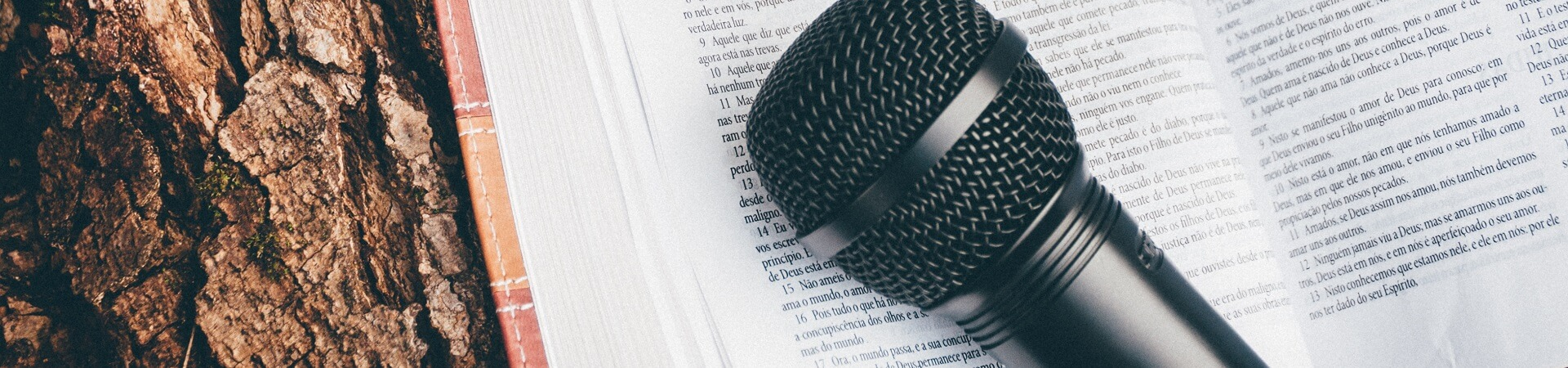 A black microphone rests atop an open book.