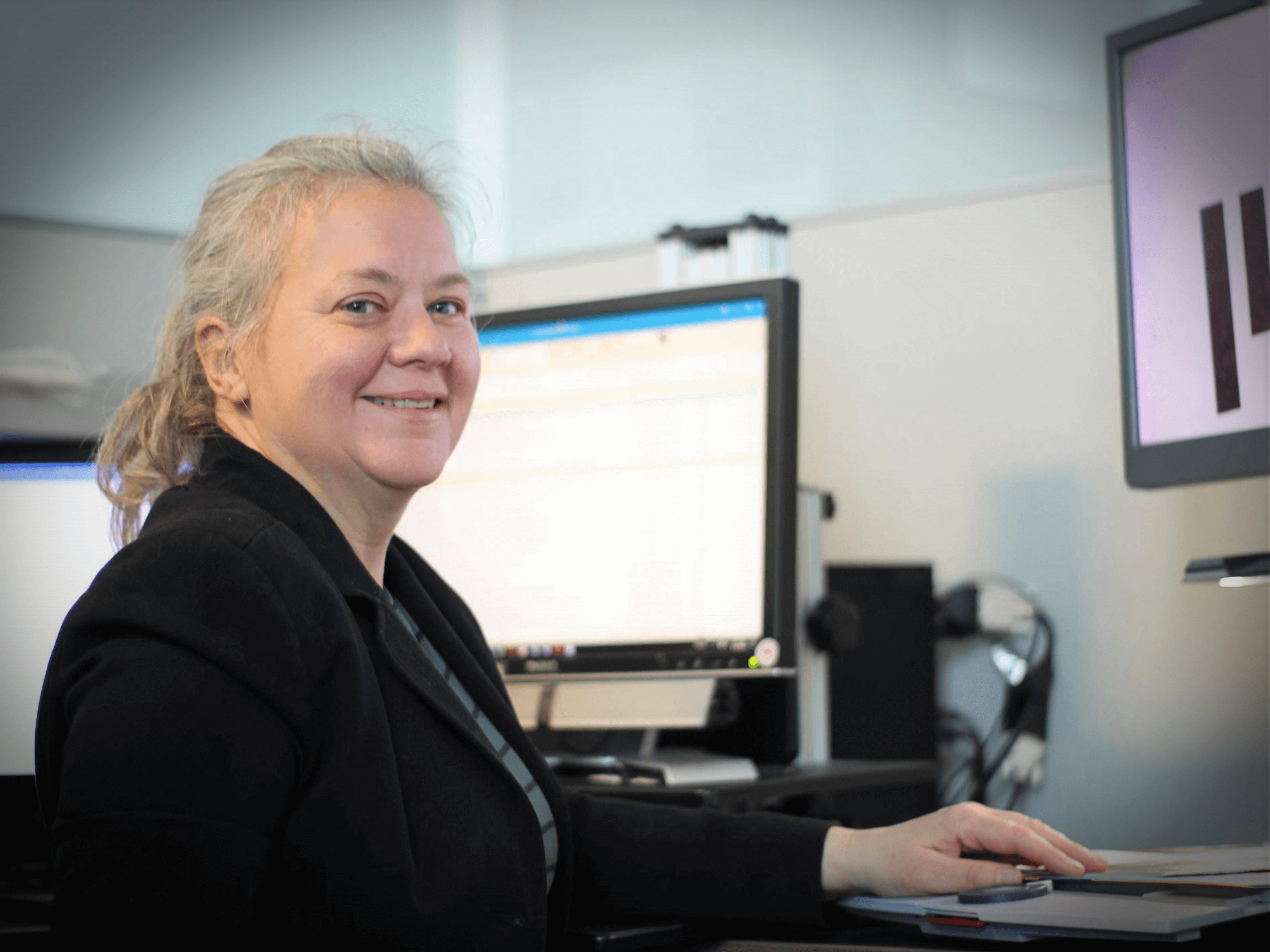 Pauline Dowell, a 2019 Carroll Society Award inductee, smiles while using a desktop video magnifier at her work station in the MIT Human Resource department.