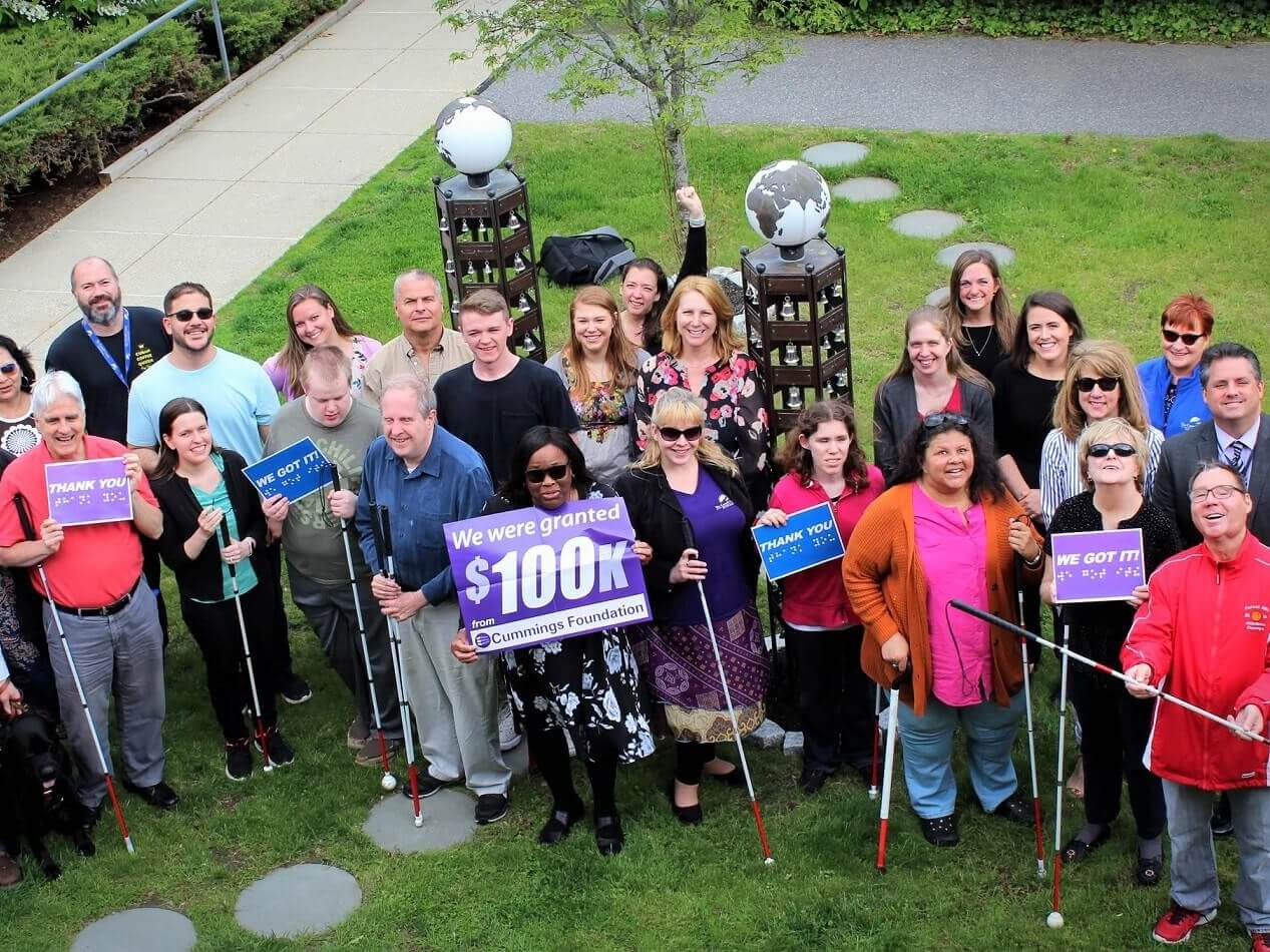 "A group of 28 Carroll Center clients and staff hold up various ""Thank You"" signage at the Carroll Center for the Blind campus in Newton, MA."