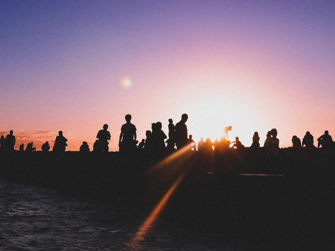 The silhouettes of many people gathered on a beach. The sun shines on the horizon just over their outlines.