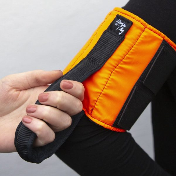 An orange Ramble Tag is worn on a guide's arm. A person's hand holds onto the black handle.