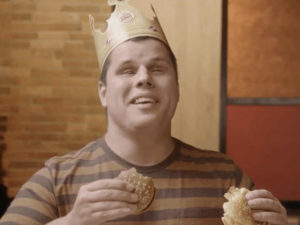In a Brazil Burger King commercial, a man who is blind wears a Burger King paper crown smiles while double-fisting two hamburgers.