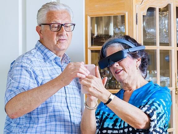 A woman wearing an assistive technology headset shows a man something on her phone.