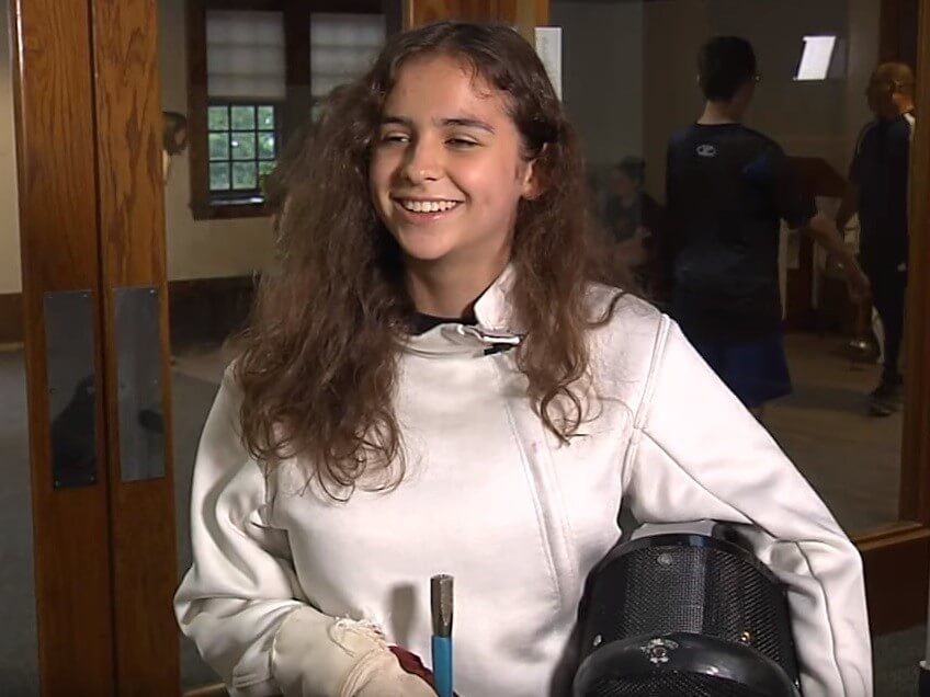A female Carroll center summer student wears full fencing equipment during a media interview.