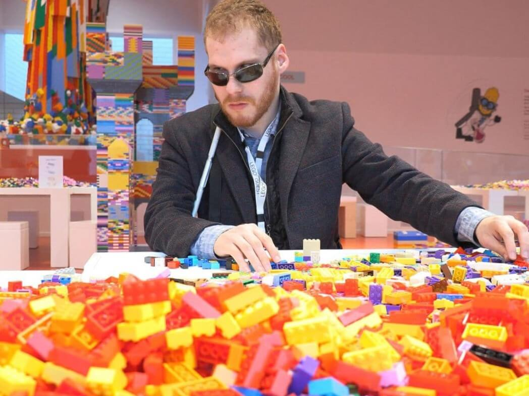 Matthew Shifrin, who has been working tirelessly for several years to spread audio and Braille Lego building instructions to children around the world, sits at a table filled with Lego blocks.