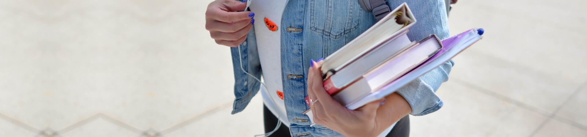 A female student wearing a denim jacket holds braille textbooks.