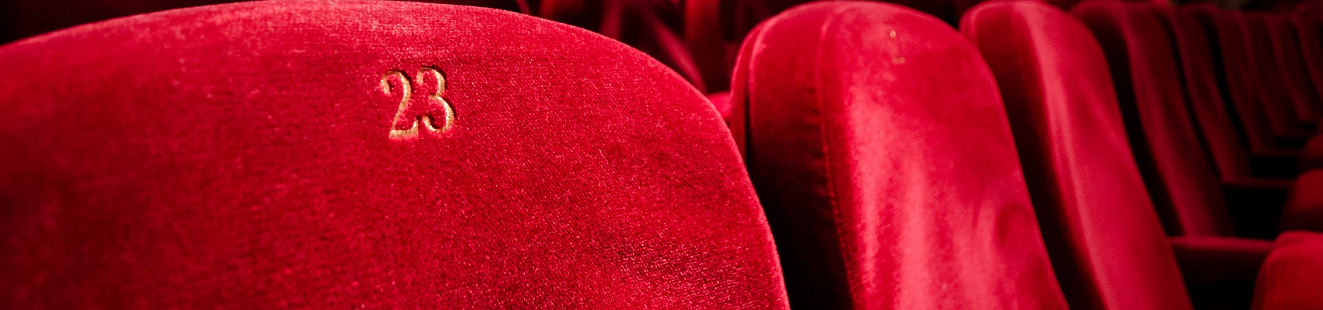 Close-up of a row of red velvet seats at a theater.