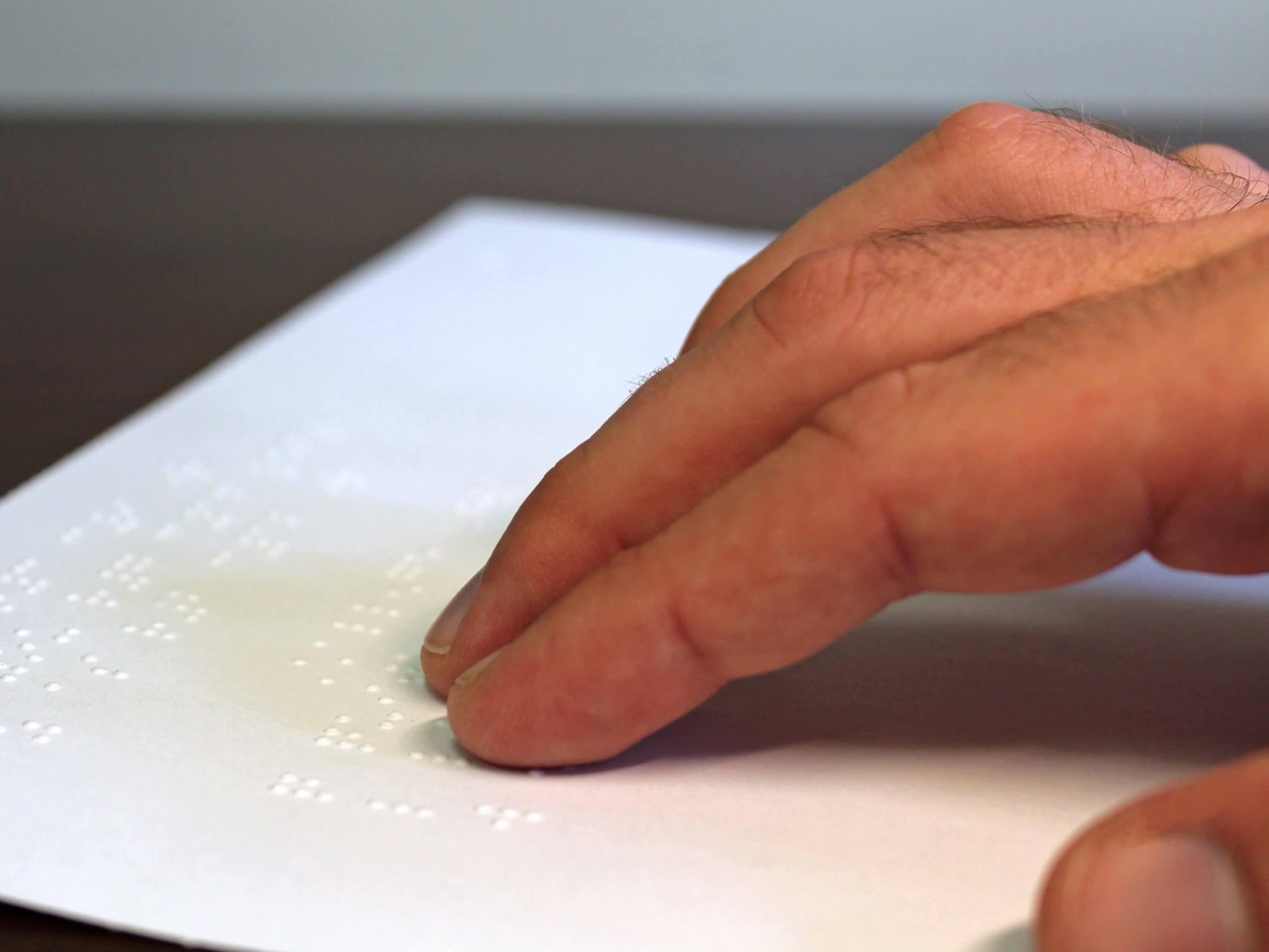 A man reads a braille sheet.