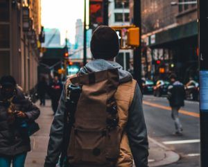 A man with his back facing the camera walks through a crosswalk in a bustling city.