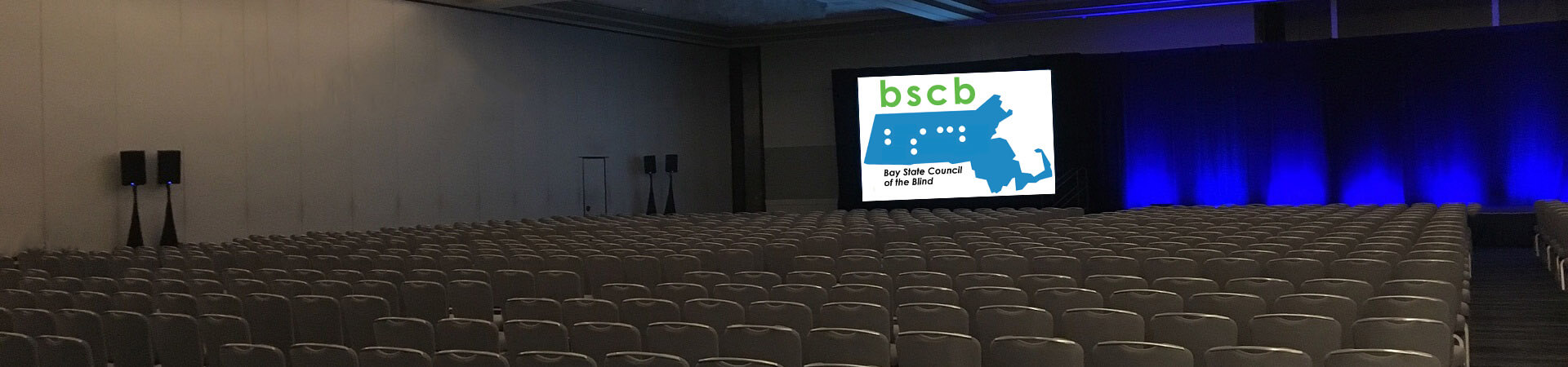 A large auditorium has a BSCB logo projected on the screen by the stage.
