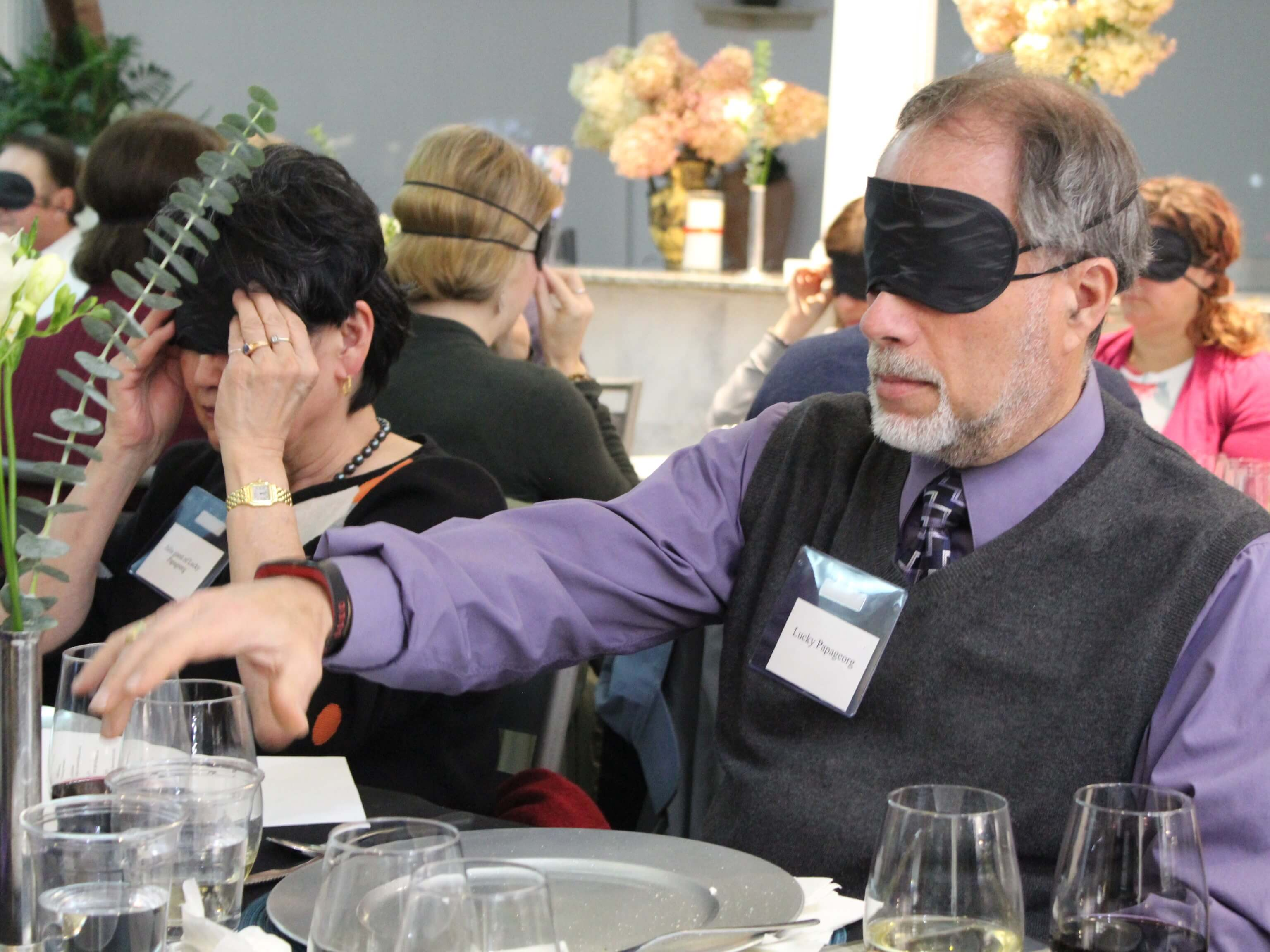 Two diners wear occluders (blindfolds) at the Farm Grill's blind food and wine tasting to benefit the carroll center. A man explores his surroundings while seated at a table.