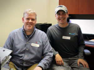 Two male volunteers smile together as they take a break from administrative work on computers at the Carroll Center for the Blind.