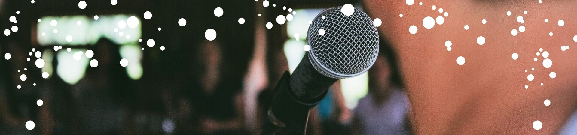 A close-up of a microphone from behind a performer's head. A blurry audience can barely be made out in the background.