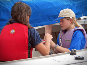 While seated in a sailboat, a volunteer helps a young woman who is visually impaired with her life jacket.