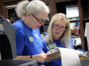 Two female volunteers glance down at a clipboard while helping with inventory in The Carroll Store.