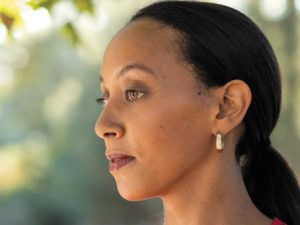 A side profile close-up of deafblind lawyer and activist, Haben Girma.