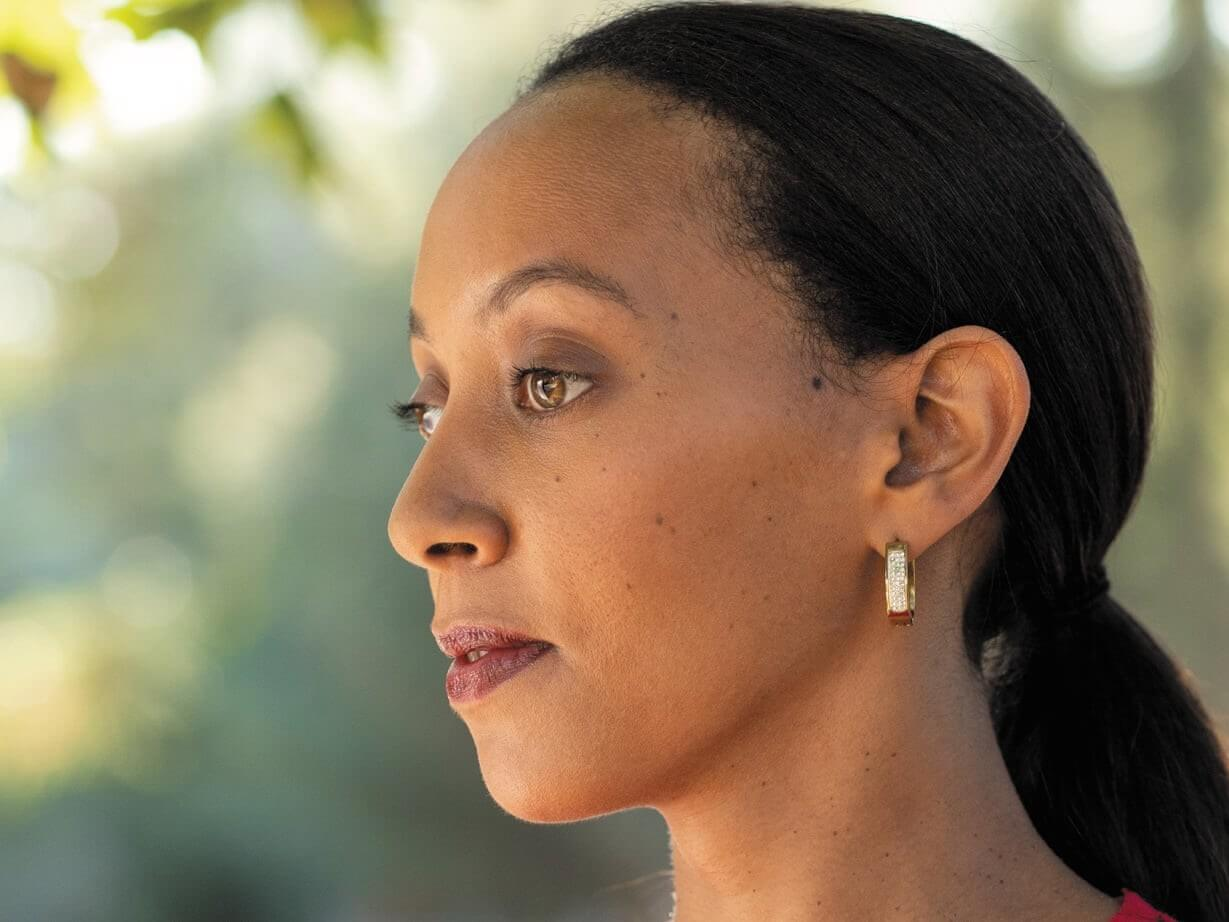 A side-profile close-up of deafblind lawyer and activist, Haben Girma.