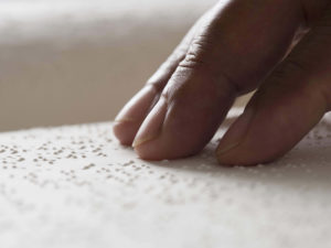 A hand rests on a sheet of braille.