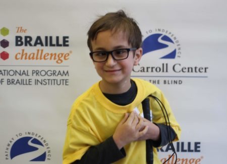 Apprentice group winner, Benjamin Silva, wears a yellow braille challenge shirt as he poses in front of a braille challenge banner.