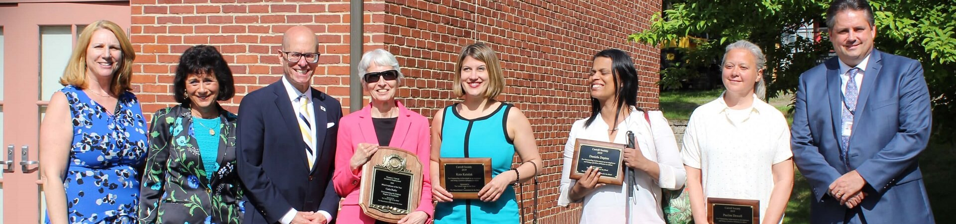 Carroll Society winners from 2019 stand together holding their awards.
