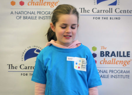 Freshman group winner, Hannah Gevers, wears a blue braille challenge shirt and poses in front of a braille challenge banner.