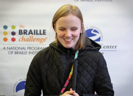 Varsity group winner, Paige Drury, smiles in front of a banner with the braille challenge and carroll center logos.
