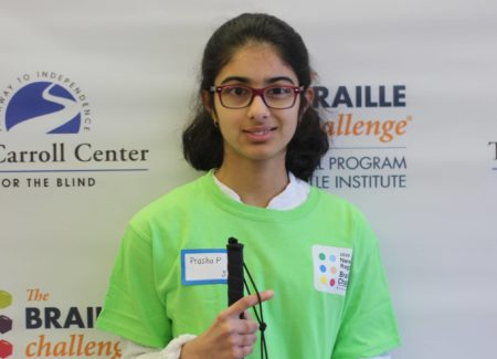 Sophomore group winner, Prasha Parajuli, poses in front of a braille challenge banner while wearing a green braille challenge shirt.
