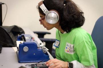 Sophomore group winner, Prasha Parajuli, types on her brailler during the braille challenge.