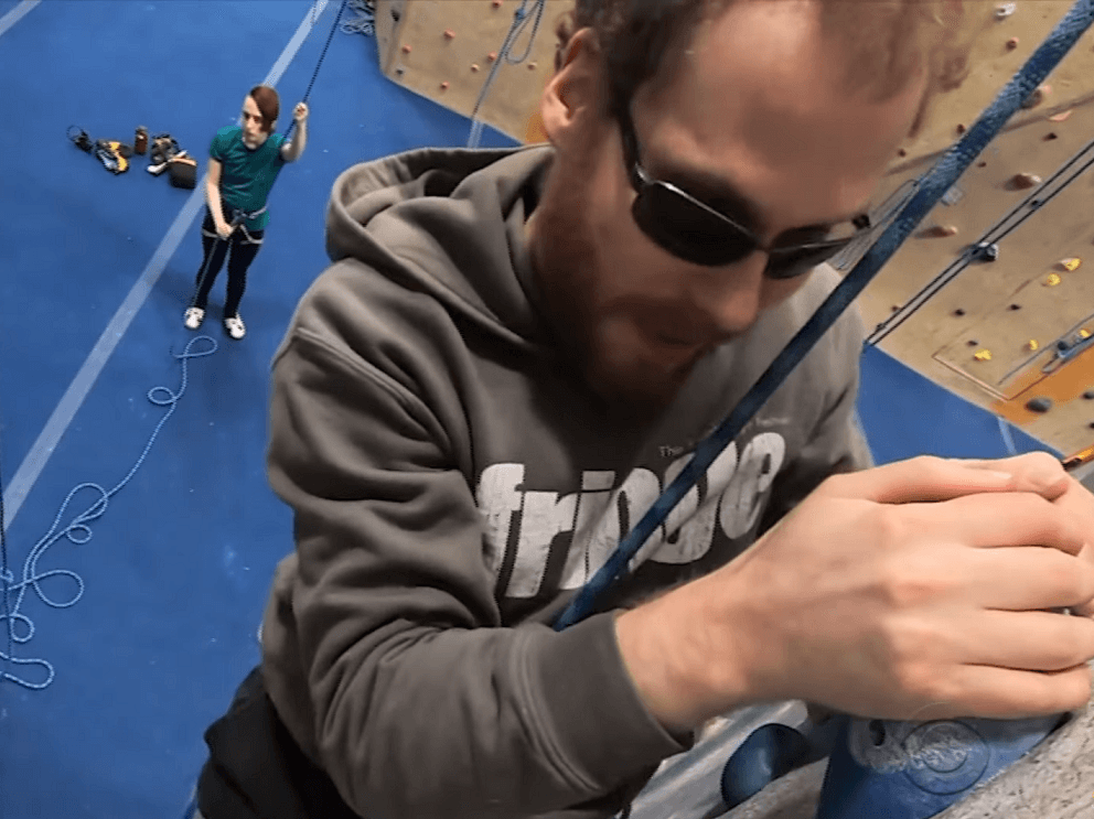 An aerial view from above Matthew Shifrin as he scales a rock climbing wall at an indoor climbing gym.